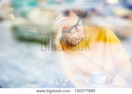 Portrait of romantic young man daydreaming while waiting for date in cafe with bouquet of flowers and cup of coffee