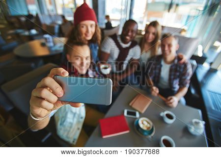 Group of friends taking selfie on smartphone while gathered together in lovely coffeehouse with panoramic windows, focus on foreground