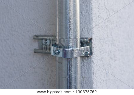 Steel Pipe Electric Wire with holder and screw on concrete wall background