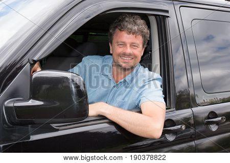handsome forties man in black van with smile