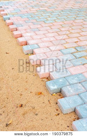 Colored brick paving stones in construction process. Outdoors.