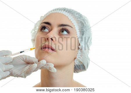 close-up portrait of a young girl in the medical CAP which has raised his eyes up and the doctor makes a prick on her face isolated on white background.