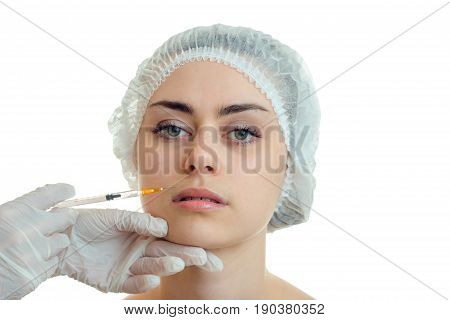 Portrait of a beautiful girl without makeup which cosmetologist doing facial injections is isolated on a white background close-up