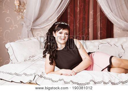 Portrait of attractive brunette on the bed indoors