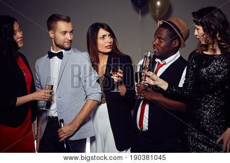 Multi-ethnic group of stylish friends gathered together in order to celebrate New Year, they holding champagne flutes in hands, pretty young woman looking at her Afro-American friend with surprise