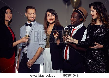 Group of smiling friends wearing trendy clothes standing against dark background with champagne flutes in hands and posing for photography