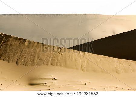 Big wandering sand dunes in desert or beach. Sand dune texture in african desert.