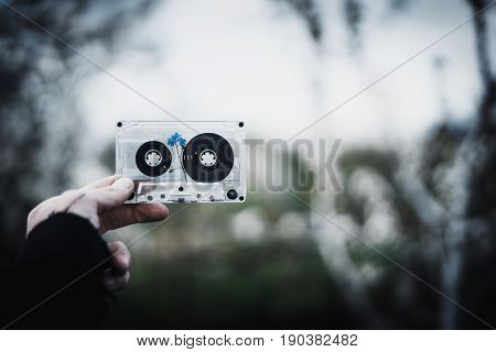 A man holds in his hand an old cassette tape with a flower inside against the sky and trees. Concept: nostalgic time.