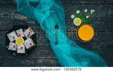 Pudding or jello and lemon with white flowers and cinnamon in a jar on wooden table background with letters and recipes. The view from the top.