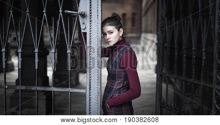 The girl with a sad look left behind the iron gates of the castle. dark scarlet color.
