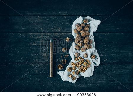 Walnut kernels and whole walnuts with a hammer on a rustic old wood table .