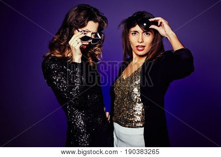 Waist-up portrait of indignant it girls looking at camera while standing against dark background