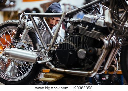 Portrait of bearded long-haired man working in garage customizing  motorcycle and repairing broken parts