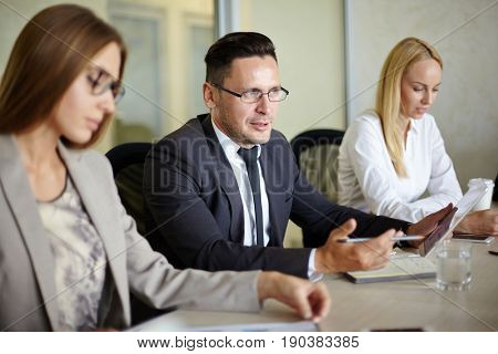 Portrait of handsome businessman in eyeglasses expressing his point of view on topical issue under discussion during meeting in modern board room