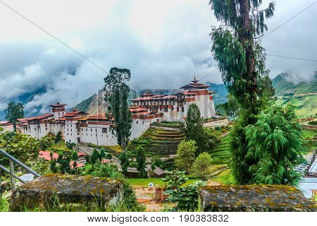 View of Trongsa Dzong with foggy hills Bumthang Bhutan Asia. Misty day in Bhutan.