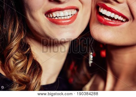Close-up shot of female dazzling smiles, unrecognizable young women standing cheek to cheek