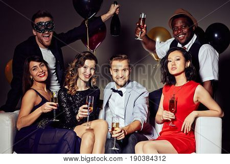 Group portrait of trendy young people sitting on sofa with champagne flutes in hands and posing for photography with wide smiles, two handsome men standing behind them