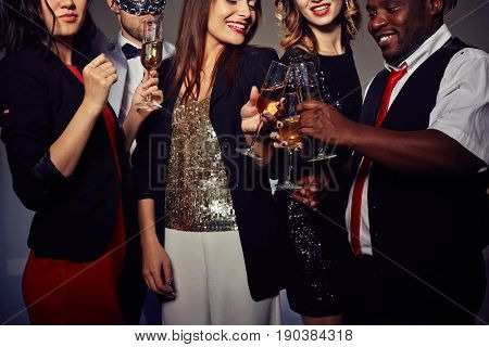 Close-up shot of stylish young people toasting with champagne flutes while standing against dark background
