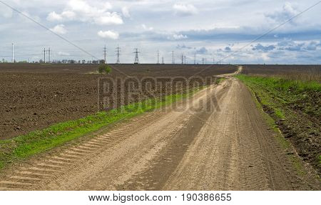 Country road between the spring fields in Ukraine.