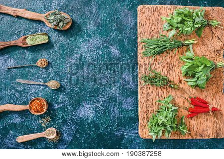 Chili peppers, cilantro, tarragon, thyme, oregano and lemon balm in the forms of fresh herbs and of dried spices  over dark blue spotty background. Top view