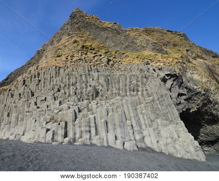 Scenic blue skies aboev the basalt column rock formations on a black sand beach in Iceland.