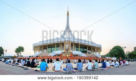 Bangkok, Thailand. - April 23, 2017 : Novice monk or priest and people sitting for meditation at Ratchamangkhala Pavillion of public park name Suan Luang Rama IX on evening time Bangkok, Thailand.