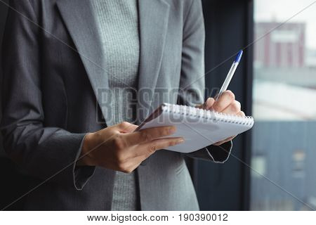 Mid section of counselor at office taking notes