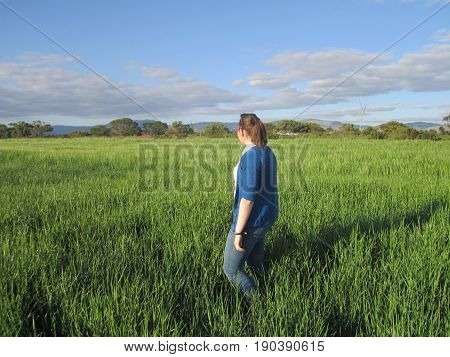 Wandering through a grassy field, deep in thought.