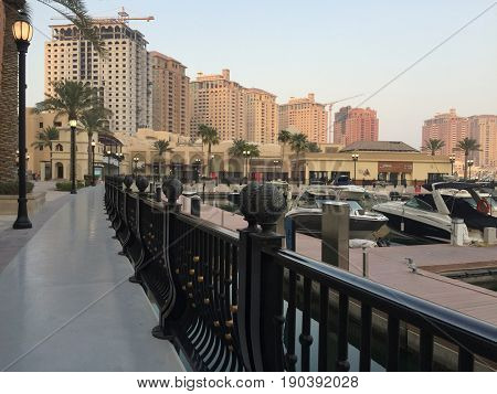 DOGA, QATAR - SEPTEMBER 14, 2016: Harbour view at the Pearl in Doha, Qatar, with yachts, boats and buildings in the background. The Pearl is an artificial island with residential buildings etc.