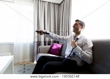 people and rest concept - happy businessman with tv remote taking off his tie at hotel room