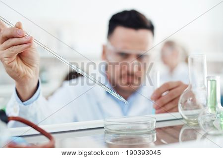 Portrait of focused scientist working on research in laboratory, performing chemical experiment dropping reactants into petri dish, focus on lab tools