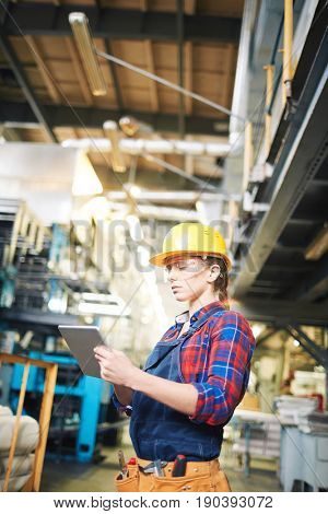 Profile view of confident female technician in protective eyewear and hardhat using digital tablet in modern factory, waist-up portrait