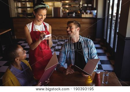 Beautiful waitress taking order at restaurant