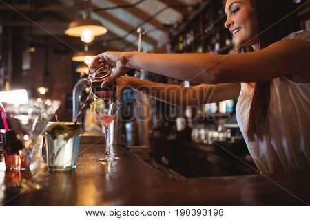 Pretty bartender pouring a cocktail drink in the glass at bar
