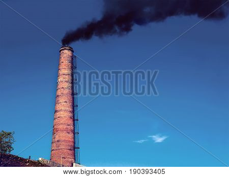 Factory chimney A factory chimney with rising smoke under a blue sky. Pipe from heat power stations