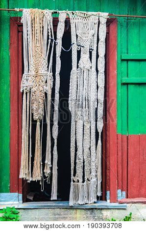 Wooden facade of an old wooden original house. Homemade curtain at the entrance to the house