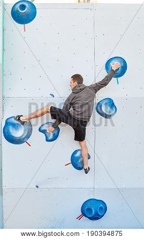 man climber climbs a bouldering problem on climbing gym. man mekes hard wide move. Climbing competition