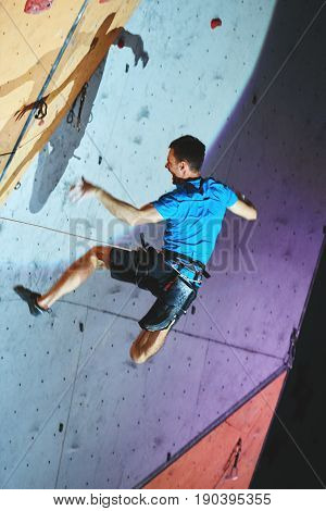 man climber climbs with rope on climbing gym. man mekes hard wide move and falling. Climbing competition