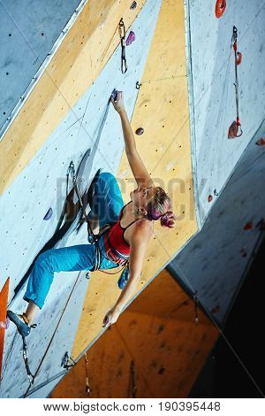 woman climber climbs with rope on climbing gym. woman mekes hard wide move. Climbing competition