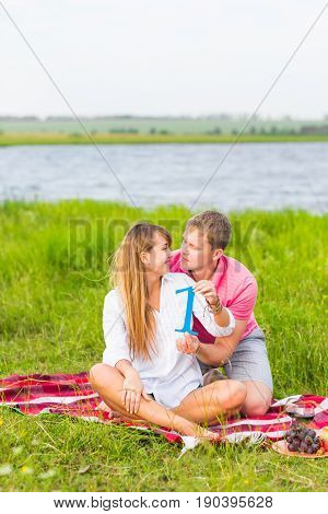 Man and woman holding the number 1 in nature. Concept of numbers, measurement, amount, quantity, accounting and mathematics.