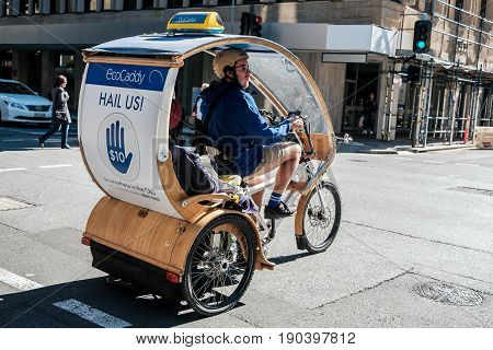 Adelaide Australia - May 5 2017: Green eco taxi EcoCaddy tricycle riding with passengers across Pirie Street on a day