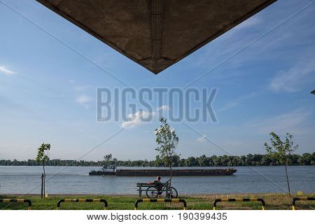 BELGRADE SERBIA - JUNE 06 2017: Young man relaxing in front of Danube river in Belgrade on Donji Dorcol district a barge passing by on the water