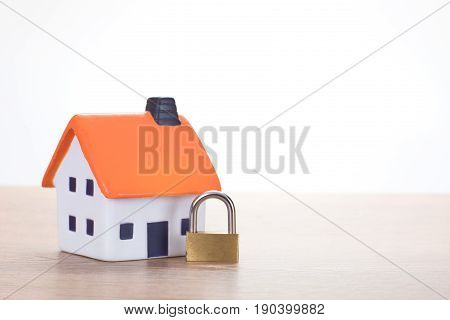 Locked brass padlock with a model house in a concept of ownership security insurance risk or foreclosure by the bank with copy space alongside