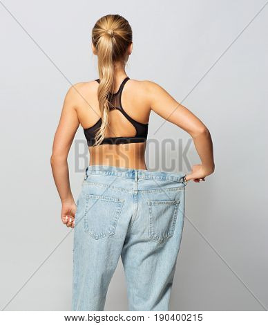 fitness, diet, weight loss and people concept - young slim sporty woman in oversize pants