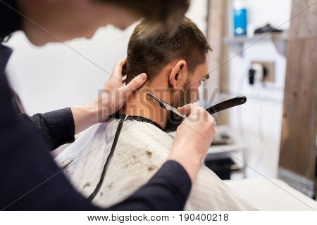 grooming and people concept - man and barber with straight razor shaving neck hair at barbershop