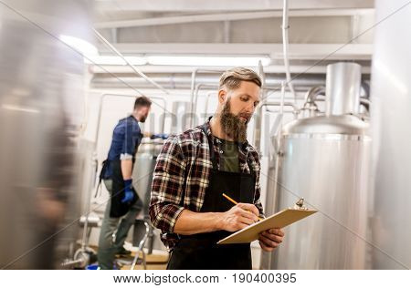 manufacture, business and people concept - men with clipboard working at craft brewery or beer plant