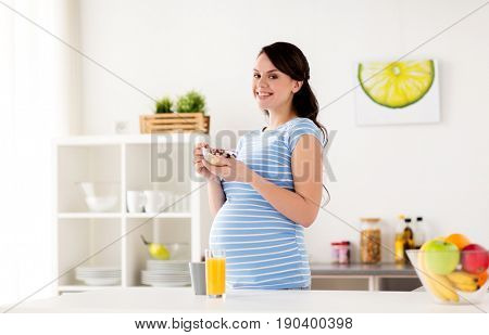 pregnancy, people and healthy eating concept - happy pregnant woman with muesli for breakfast at home kitchen