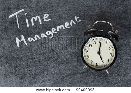 Time Management concept with an old fashioned bell alarm clock on a blackboard with handwritten text and copy space