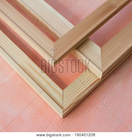 Corners of wooden stretchers. Subframes for gallery wrapped canvas. Pink background.