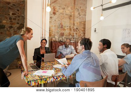 Young woman managing a team meeting in a boardroom, close up